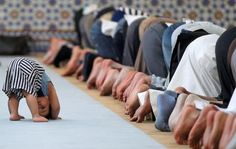 * Midday Prayers by theatlantic: A child leans down near members of the Muslim community attending midday prayers at Strasbourg Grand Mosque in Strasbourg, France on the first day of Ramadan, July (Image credit: Reuters/Vincent Kessler)