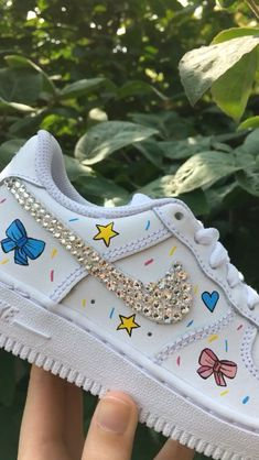 Confetti cuteness junior Nike Air Force 1 - Junior White Nike Air Force 1 trainers hand painted with bows, stars, hearts and confetti finished off with a Swarovski Crystal swoosh Nike Source by paulineboras - Custom Painted Shoes, Custom Shoes, Nike Custom, Sneaker Diy, Nike Shoes Air Force, Cute Sneakers, Shoes Sneakers, Aesthetic Shoes, Hype Shoes