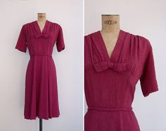 Beautiful vintage textured maroon knit jersey dress with v gathered neckline, slightly padded shoulders and bow detailing. Braided belt,