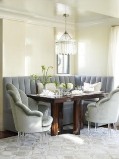 Cosy dining corner looking plush - padded seating in soft grey & a chandelier for understated elegance.