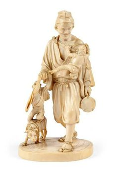 A Japanese ivory okimono of an entertainer, late Meiji, with a dog at his feet and two monkeys clambering over a piece of fruit in his hand, a drum in the other, signed. Height 21 cm