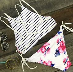 Adorable and versatile bikini set features high-neck halter crop top with strappy back, and side-tie bikini bottom. One side is blue and white striped, and the other side features a tropical pink hibiscus floral print. Wear as a striped set, as a floral set, or mix and match the top and bottoms to create several different looks.