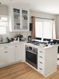 White kitchen with glass door display cabinet and peninsula with oven and cooktop.