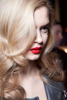 Classy red lips with a black heart beauty mark drawn under the eye