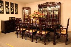 Chinese dining room with dining table, dining chairs, and wooden and glass cabinets.