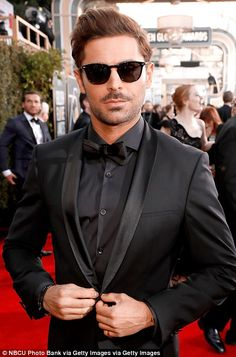 Slick: Zac cut a cool figure as he posed for cameras, and later accessorised with dark sunglasses as he hit the carpet