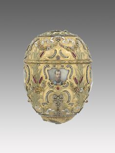 """The Emperor Nicholas II gave this Egg to his wife, the Empress Alexandra Fedorovna for Easter 1903. It commemorates the 200th anniversary of the founding of Saint Petersburg by Peter the Great. Its body of varicoloured gold is in the rococo-revival style and was inspired by a French nécessaire with a clock that is still in the Hermitage. The body of the Egg is rich in symbolism. In Russia roses and laurel leaves represent triumph and pride. The bulrushes shown in our image to the left and…"