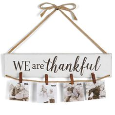 "Painted mango wood photo or card holder features painted ""WE are thankful"" sentiment and jute cord with four wood clothespins for hanging photos, cards, or invitations. Arrives with burlap ribbon and"