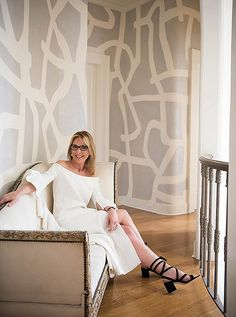 Interior designer Tara Shaw rests on a carved framed linen sofa on the upstairs landing of her stunning New Orleans estate home.