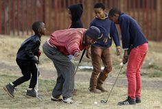 Wynand Morudu, second from left, points out a hole during the a game of golf at a park in Katlehong township, east of Johannesburg, South Africa, Thursday, July 16, 2015. (AP Photo/Themba Hadebe)