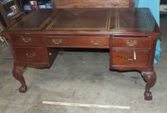 LARGE OFFICE DESK WITH THREE SECTIONED TOP, BALL AND CLAW FEET AND BRASS HARDWARE. THE DESK HAS TWO DRAWERS ON EITHER SIDE AND A CENTER DRAWER WITH A DRAWER FACE THAT FOLDS DOWN. SHOWS SOME SCUFFING/WEAR. MEASURES 2FT 6 IN TALL, 4 FT 10 IN WIDE AND 2 FT 5.5 IN DEEP.