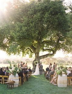 A beautiful tree becomes is the perfect focal point for this outdoor wedding ceremony. #wedding #backdrop