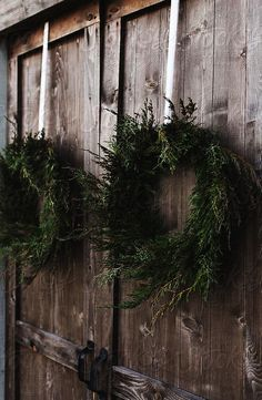 Beautifully made natural pine and cypress wreaths hanging on barn doors for the holiday season providing rustic christmas inspiration and Scandinavian christmas ideas for the holidays wreath creative Natural Christmas, Noel Christmas, Country Christmas, Simple Christmas, All Things Christmas, Winter Christmas, Christmas Wreaths, Xmas, Christmas Ideas