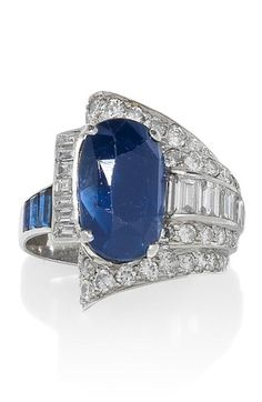 An Art Deco sapphire and diamond dress ring, circa Of odeonesque design, the oval-cut sapphire set within a scrolling oblique mount decorated with baguette and brilliant-cut diamonds, diamonds approximately carats total. Bijoux Art Deco, Art Deco Jewelry, Jewelry Rings, Fine Jewelry, Jewelry Design, 1920s, Antique Jewelry, Vintage Jewelry, Sapphire Jewelry