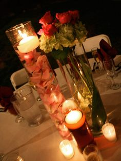 variation of centerpieces featured a vase with submerged orchids, a small rose arrangement, and a smaller vase with a floating candle. Budget Saver: To save money on flowers, pair smaller arrangements with candles to create a beautiful glow during dinner.