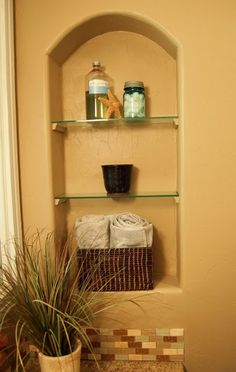 Behind the toilet? Add trim pieces to slide shelves onto wall?