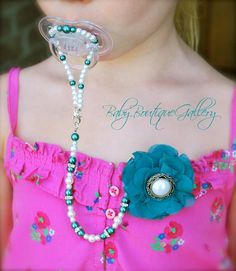 Baby Boutique Teal Flower with White Pearl 4-in-1 Beaded Pacifier Holder. $19.99, via Etsy.