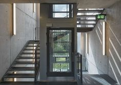 Metal staircase wrapped around a central glass lift shaft, in the Sport Hotel, Klingenthal, Germany