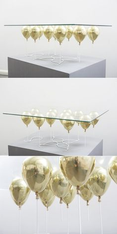 This is a truly designer coffee table. Gold enamel balloons look like they are keeping the clear glass tabletop afloat for a luxurious – and whimsical – effect.