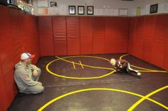 Wrestler Stevo Poulin, 8,  practices his moves with his father Steve Poulin in the wrestling room his dad built him in the basement of his home