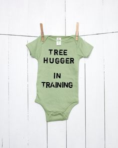 Tree Hugger in Training Organic Cotton One Piece Infant Bodysuit in Avocado Green is hand stamped in distressed grunge lettering (letters are