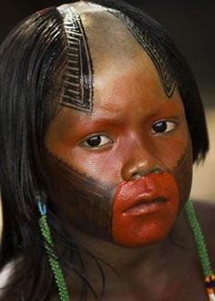 South America | Portait of a young Kayapo girl with a decorated face, Brazil
