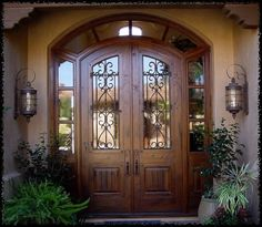classy custom double wood doors with wrought iron and old country feel