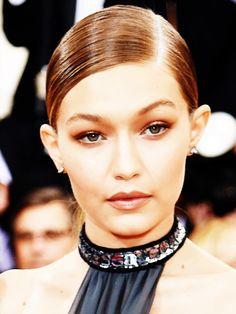 Gigi kombiniert ihr monochromes Make-up in Brauntönen zu einem Sleek-Chignon und Glitzer-Scheitel.