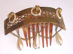 This is a beautiful Peigne d'Alger. A gilt silver tiara has openwork in the middle and holds three seed-pearl circles. Hanging on the bottom are two interlocking chains and three faux pearl pendants. The decoration is hinged to a horn comb. c. 1880.