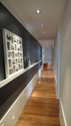 Hallway. O rodapé branco cria um contraste lindo com o cinza chumbo desse corredor. A prateleira na mesma cor também dá um destaque para o quadro de fotos. O projeto de iluminação e o piso de madeira também são lindos