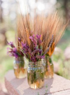 "#Lavender and #Wheat    Cute centerpiece idea! Could see changing it to beach grass & hibiscus or some other tropical flower for a beach themed wedding! With seashells in the water of the mason jar and a beige or ""beachy"" colored ribbon around the top of the jar!"