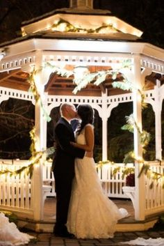 A special moment at the beautifully decorated Grain House Gazebo during a holiday wedding.