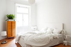 bottles with candles, beautiful wood, beautiful messy bed. love the white walls and bedding.