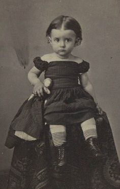 19th century toddler holding her porcelain head doll and looking very suspicious about the whole photo thing
