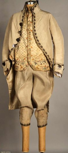 GENTS 3 PIECE SILK SUIT, c. 1775-1785  Coat & breeches putty faille, metallic bobbin lace trim, large cut-steel buttons on jacket, small self covered on breeches; cream satin sleeveless waistcoat w/ colorful floral embroidery,