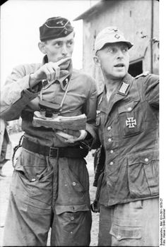 Northern France, June 21, 1944: Panzer driver with injured left hand holding the map and army lieutenant determine direction at an unidentified location. By late June 1944, the Allied forces fanning out from Normandy were being deployed on a broad-front mass attack on German forces in France.