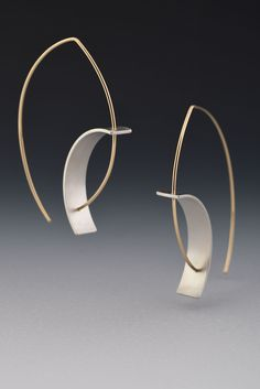 Tension Earring by Hilary Hachey. The convex earwire combined with the concave element create the tension for which this earring is named. The element is sterling silver, and it is available with a matte finish or an oxidized one. The ear wire shown is 18k yellow gold.