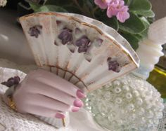 Hand holding a fan with applied violets (flowers other than roses are unusual)