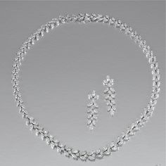DIAMOND DEMI-PARURE, Of foliate design, set with graduated marquise-shaped and brilliant-cut diamonds, length approximately 380 mm, together with a pair of pendent earrings en suite, post and butterfly fittings.