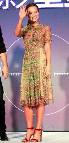 ALICIA VIKANDER in a girly floral embroidered mid-length Gabriela Hearst dress with velour magenta sandals at a Jason Bourne press conference in Beijing, China