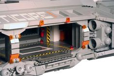 The fighter bays were an engineering nightmare, because the midsection of the ship has no wall on one side and very little interior support. Its strength comes from Technic frames in both the floor and ceiling, and three layers of solid brick beneath the floor. The garage door leads to the maintenance area for the fighters.