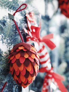 Dekoracja z filcu i szyszki zawieszona na drzewie.