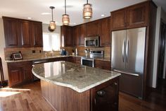 Earth-tone kitchen remodeled with Walnut cabinetry, granite countertops, Hickory flooring & Travertine backsplash. by Carpentry By Chris