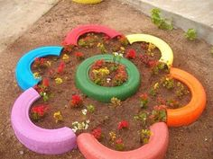 Cute flower bed made out of tires painted cut in half one whole one for the center.