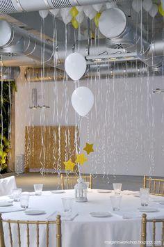 Infla globos con helio,átalos con cintas o lazos y suéltalos sobre la mesa para decorar el techo