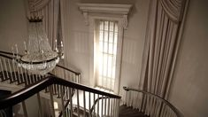 """Mansion from """"American Horror Story, Coven"""".  White on white.  Whitewashed hardwood floors and white walls.  White and shades of white furniture outlined in black and different shades of wood."""