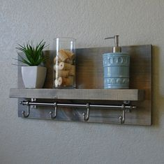 Handmade bathroom shelf with satin nickel finish rail towel hooks. A perfect addition to any home bathroom or apartment. Made from solid wood. It has been lightly sanded down, then stained and sealed with a beautiful weathered gray finish. This piece does not include the accessory items as shown in the pictures. The color of the stained wood captured in the photos might vary slightly. Dimensions: 23 in wide x 11.25 in tall x 4/6 in deep (shelf 3.5/5.5 in deep) Keyhole hangers a...