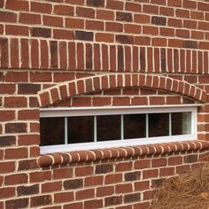 Pine Hall Brick Old Yorktown authentic tumbled brick with Ivory Buff Mortar. ST-5 Sill Brick are used along with a protruded headers to create and arch over this basement window.