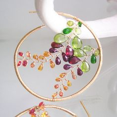 .......stained glass....... 18 gauge 14k gold filled wire lengths have been forged into hoop style earrings and adorned with wire wrapped vines of vesuvianite, peridot, chrome diopside, red garnet, rhodolite garnet, and golden and orange sapphires. 18 gauge is a little thicker than 20 gauge. 20 gauge is what I normally use for ear wires and hoops with extended post. If you have delicate or tender piercings these might be too thick. Length, from head to toe, is 2 1/4. Width, at widest,...