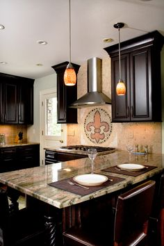 The Howland Group remodeled this Hyde Park kitchen for a busy family. With lots of custom details like the fleur-de-lis backsplash, this kitchen is stylish and functional. Dark cabinets, light granite countertops, and stainless steal appliances updated this kitchen to fit the family's design style.  Photos by Gomsak Photography